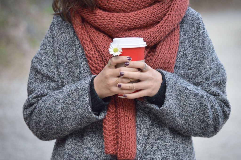 Person wearing a red knitted scarf holding a coffee cup