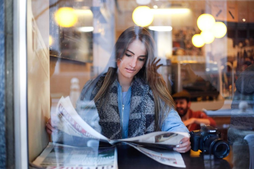 Woman reading a newspaper in a cooffee shop