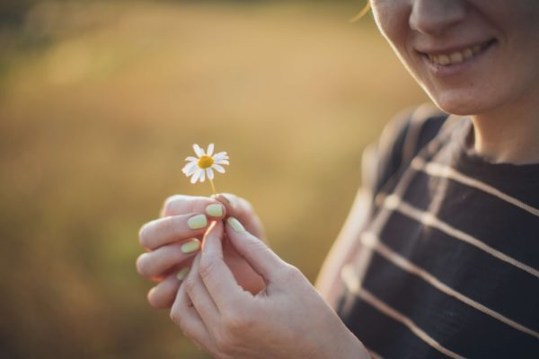 Woman holding a daisy
