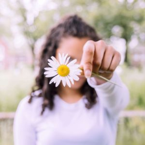 Person holding a daisy in front their face