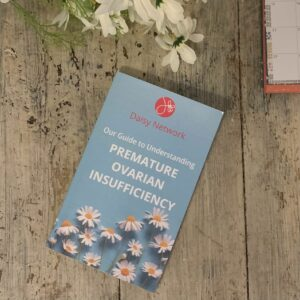 Book cover with white daisies, on a rustic wooden table